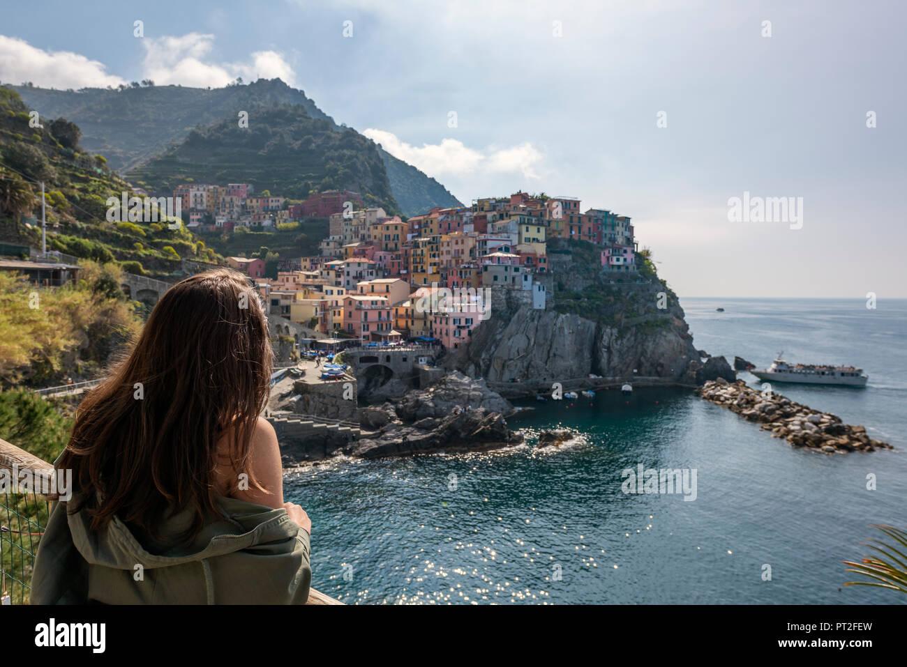 Italy, Liguria, La Spezia, Cinque Terre National Park, young woman looking to Manarola - Stock Image