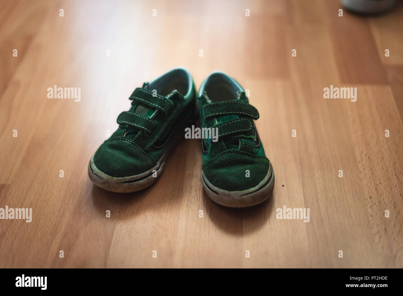 Worn and muddy pair of childs shoes on a wooden floor of a living room. - Stock Image