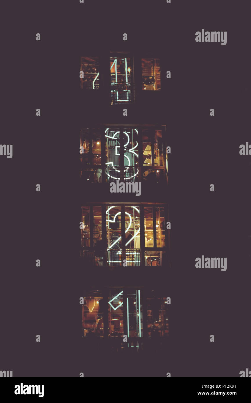 Building exterior view at night with the numbers of corresponding floors - Stock Image