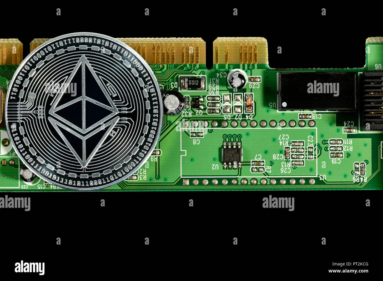Symbolic image of digital currency, silver physical coin Ethereum on circuit board - Stock Image