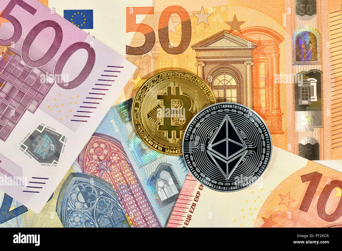 Symbolic image of digital currency, golden physical coin Bitcoin and silver physical coin Ethereum on EURO banknotes Stock Photo