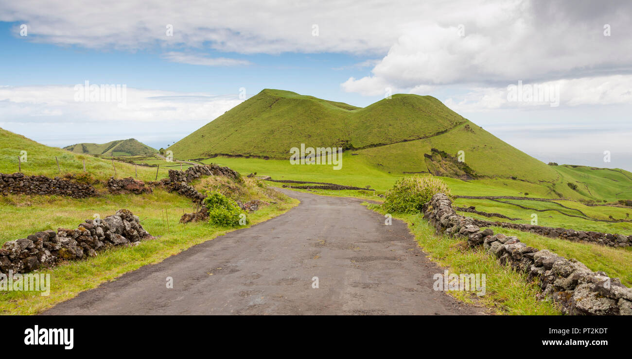 down the valley on the transversal from Madalena to Piedade, green volcanic cone at the vanishing point of the road - Stock Image