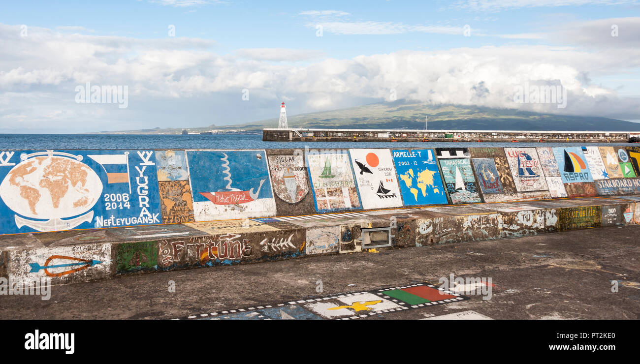 Harbor picture from the landing stage in Horta, colored paintings of the sailor arrivals, lighthouse and neighboring island Pico in the background - Stock Image