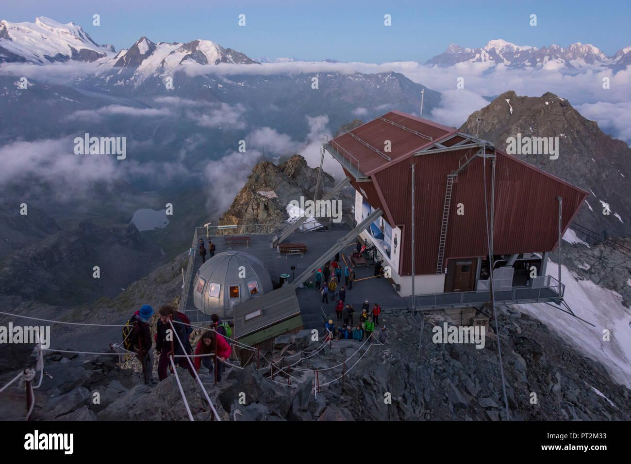 Switzerland, canton Valais, district Entremont, Verbier, sunrise, 3329 m high Mont-Fort, view on the Combin de Corbassière, people enjoying the view - Stock Image