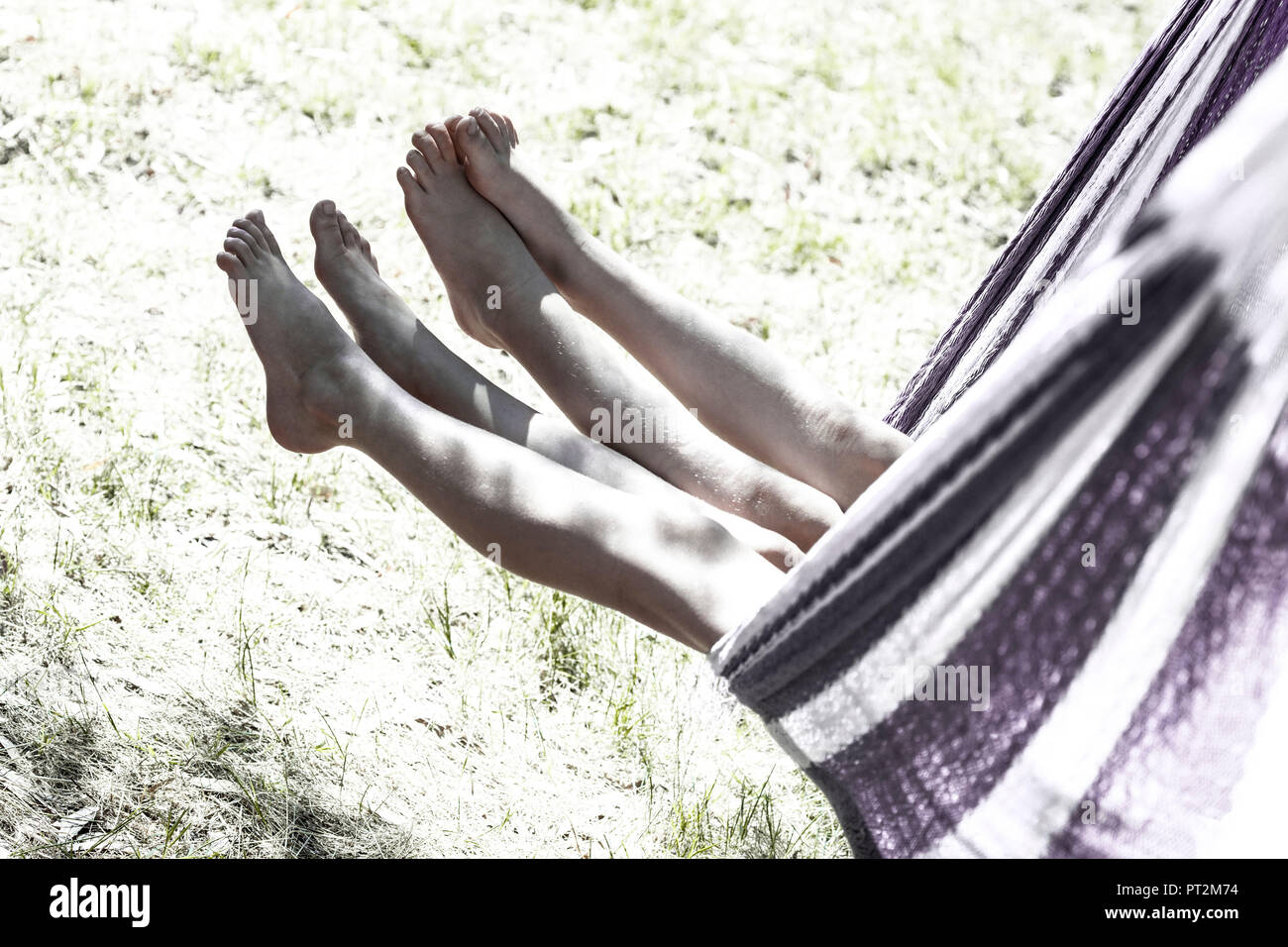 2 girls swing their legs out of a hammock while rocking Stock Photo