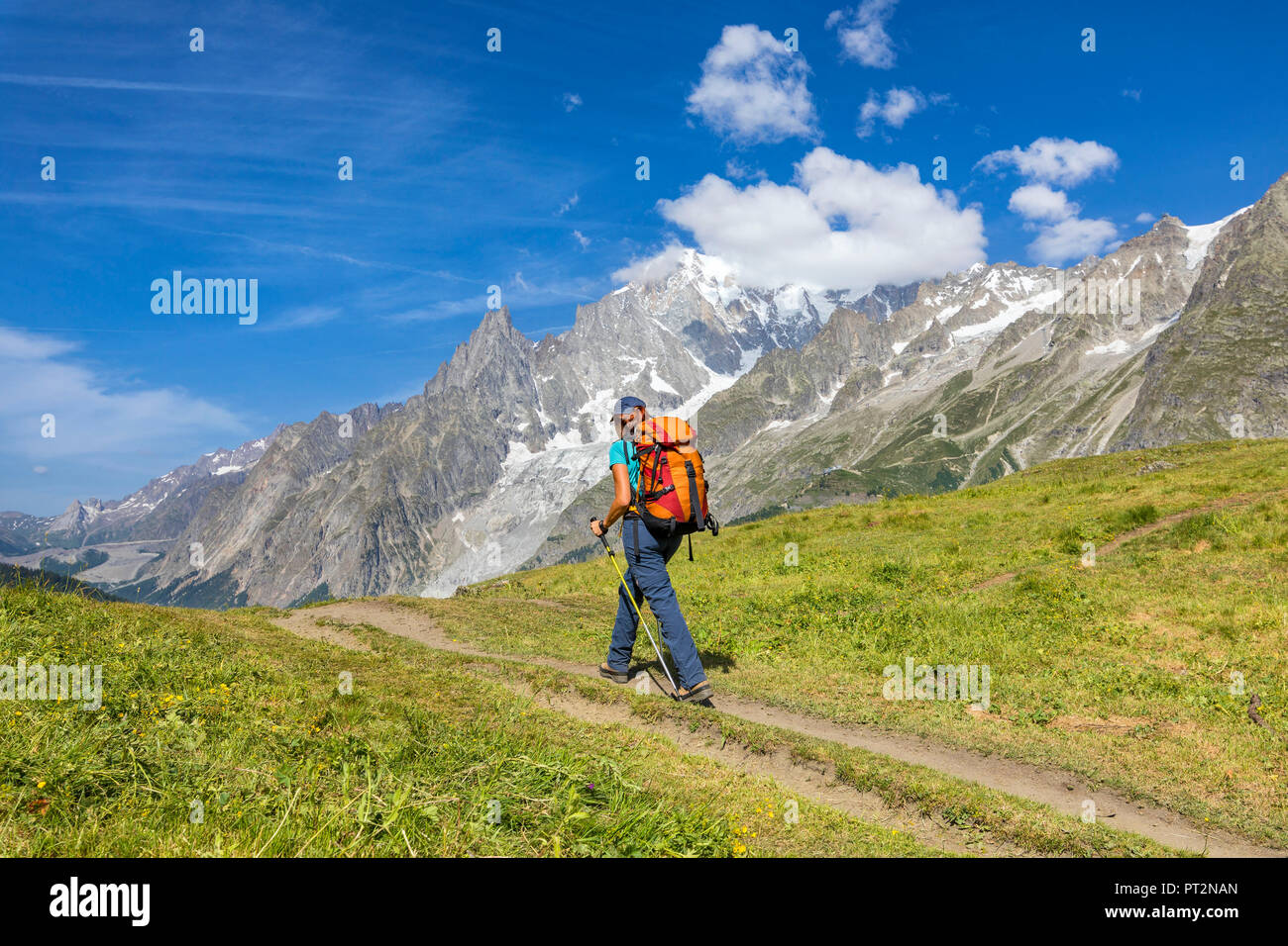 A trekker is walking in front of the Mont Blanc during the Mont Blanc hiking tours (Ferret Valley, Courmayeur, Aosta province, Aosta Valley, Italy, Europe) Stock Photo