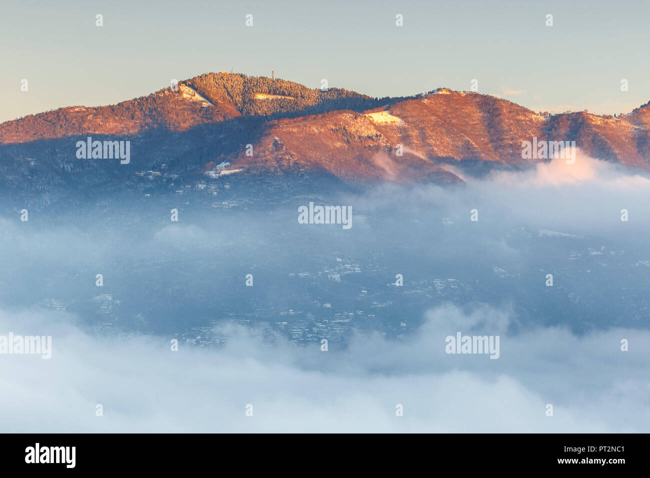 Bisbino mount rise up from a sea of clouds at sunrise, como province, Lombardy, Italy, Europe - Stock Image