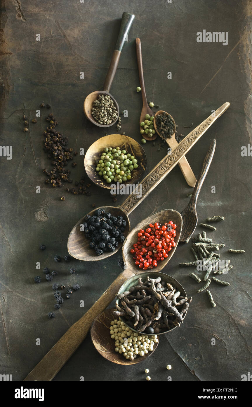 Various sorts of pepper on spoons Stock Photo