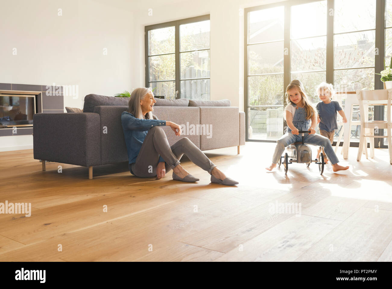 Grandparents observing grandmother, playing in livingroom - Stock Image