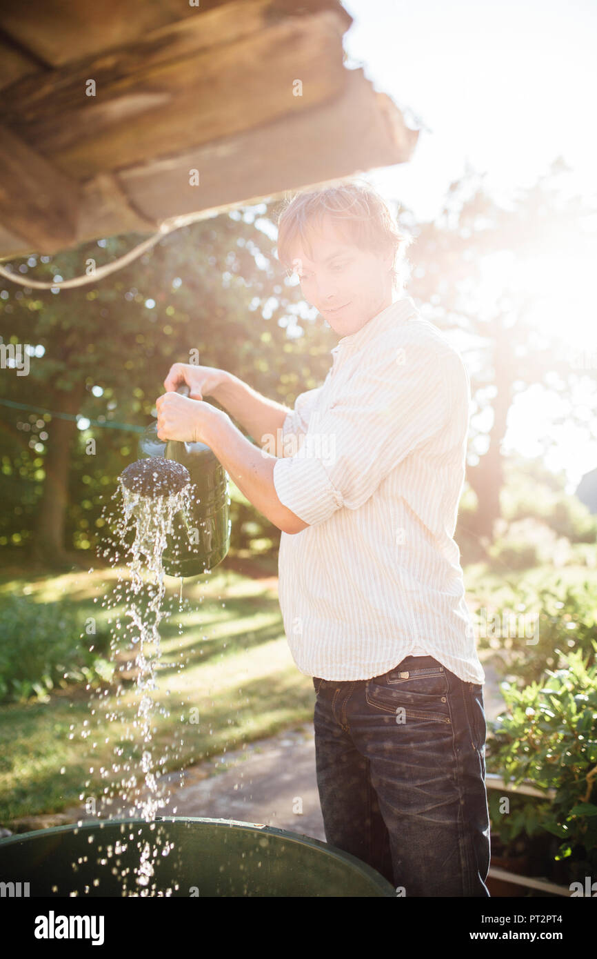 Man with watering can in garden - Stock Image