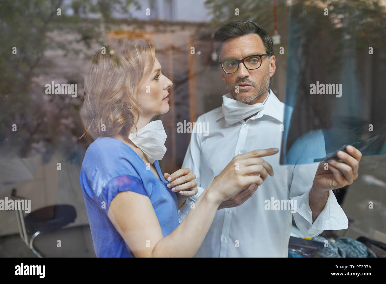 Portrait of radiologist and nurse behind windowpane looking at x-ray image - Stock Image