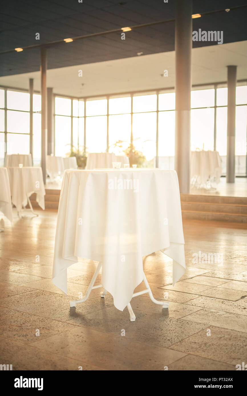 Interior with poseur tables, white tablecloths and warm sunlight - Stock Image