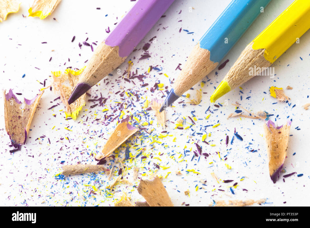 cyan magenta yellow pencils with splinter waste on white paper - Stock Image