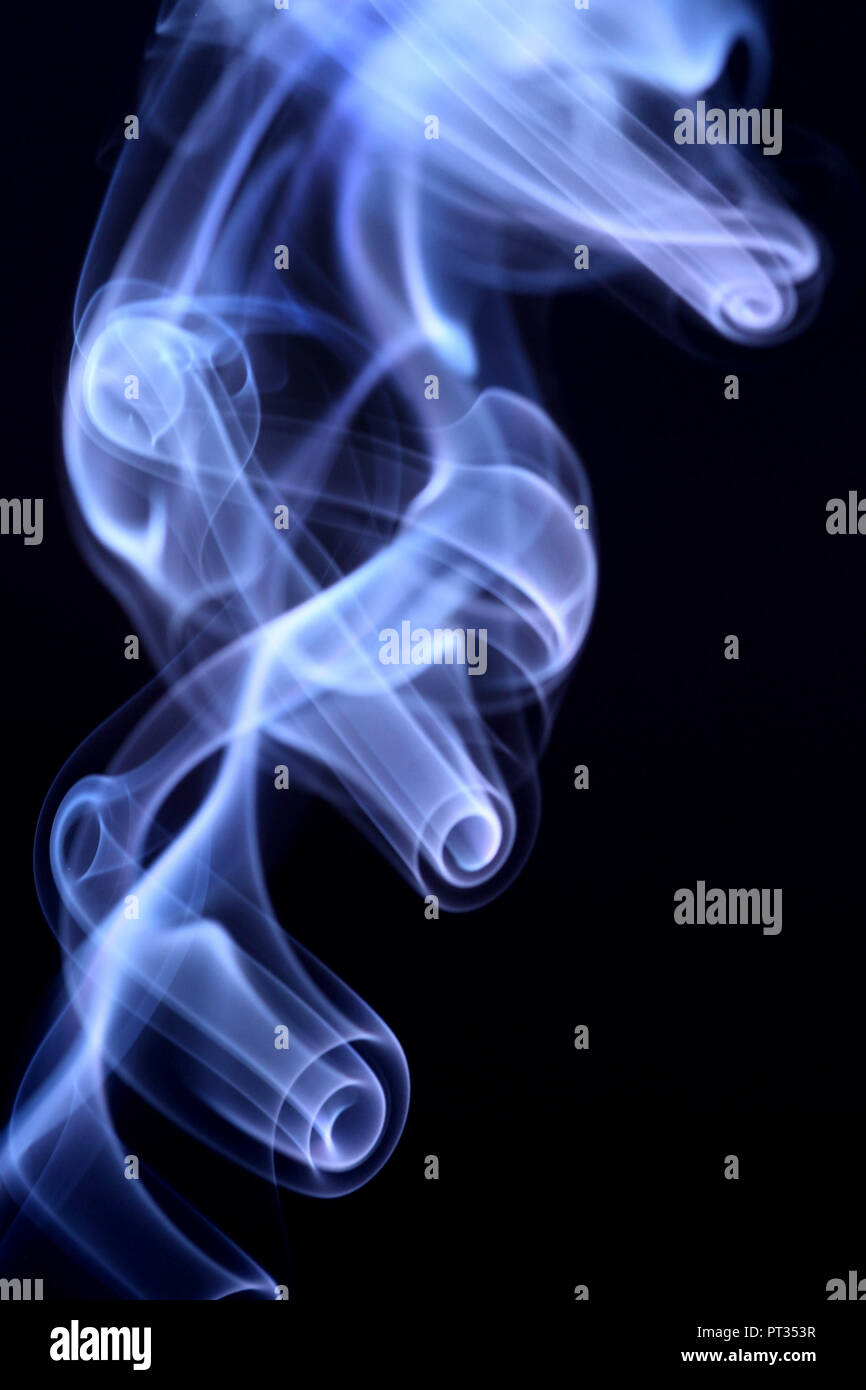 blue smoke on black background produced by a incense stick, Ordered structure close to stick, more chaotic further up, - Stock Image