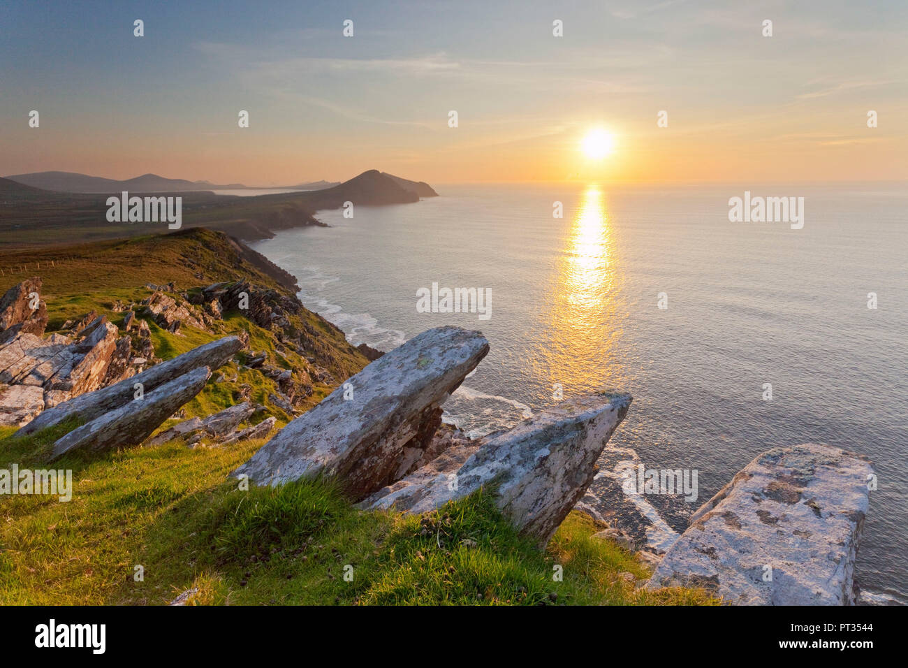 View from high cliffs overlooking the coastline of Dingle Peninsula at sunset, Taken from the western trail up to Mount Brandon, Northern Part of Dingle Peninsula, Western Ireland, - Stock Image