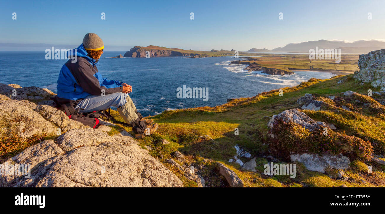 man looking out on the coastline on a clear early morning, location: dingle peninsula in co, kerry, western ireland, Waymont near Graigue, 52, 151437, -10, 475927 Stock Photo