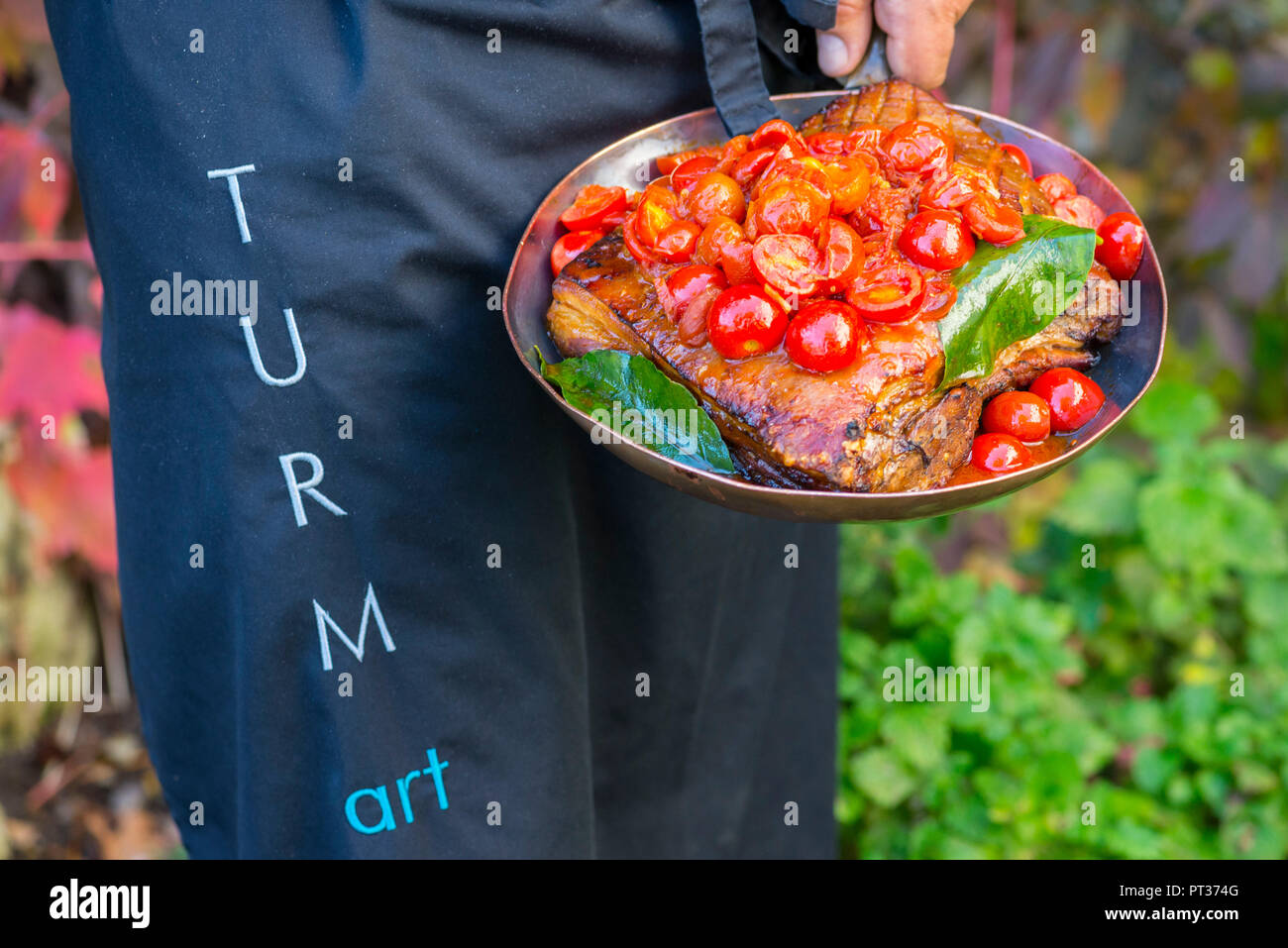 Chef with braised pork belly with tomatoes, Romantik Hotel Turm, Fiè allo Sciliar, Alpe di Siusi, Eisacktal, South Tyrol, Italy - Stock Image