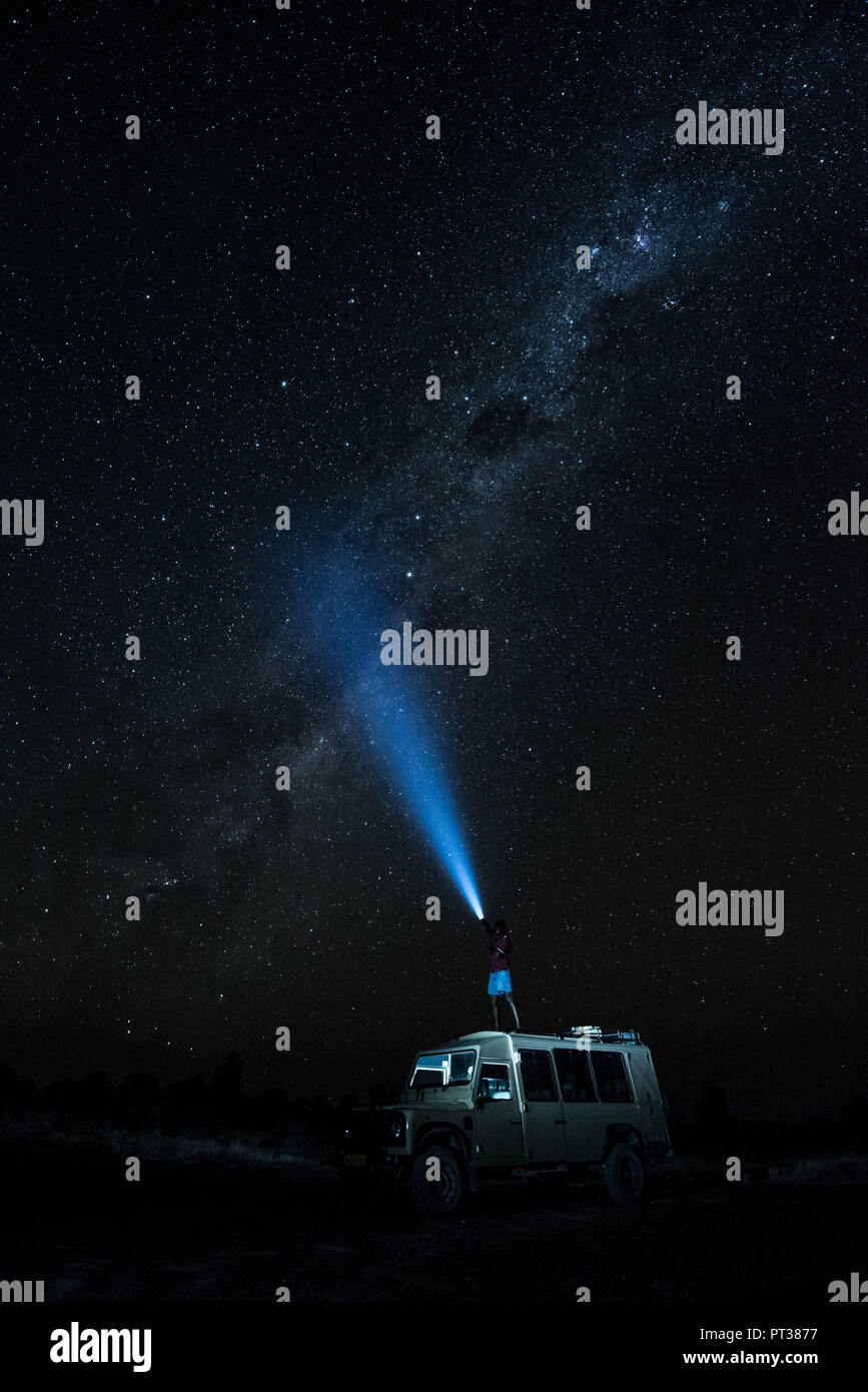 Man standing on a jeep and shining with a flashlight in the starry sky, creative long exposure, Namibia, Africa - Stock Image
