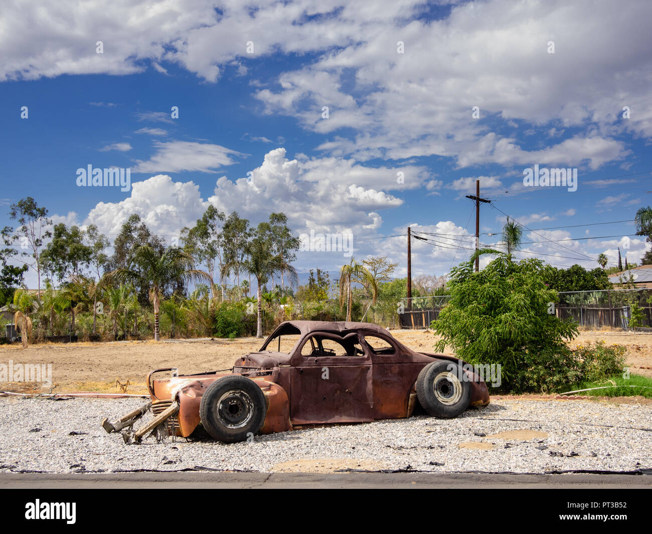 Rusted abandoned car at Wigwam Motel on Route 66 in San Bernardino , California, USA. - Stock Image