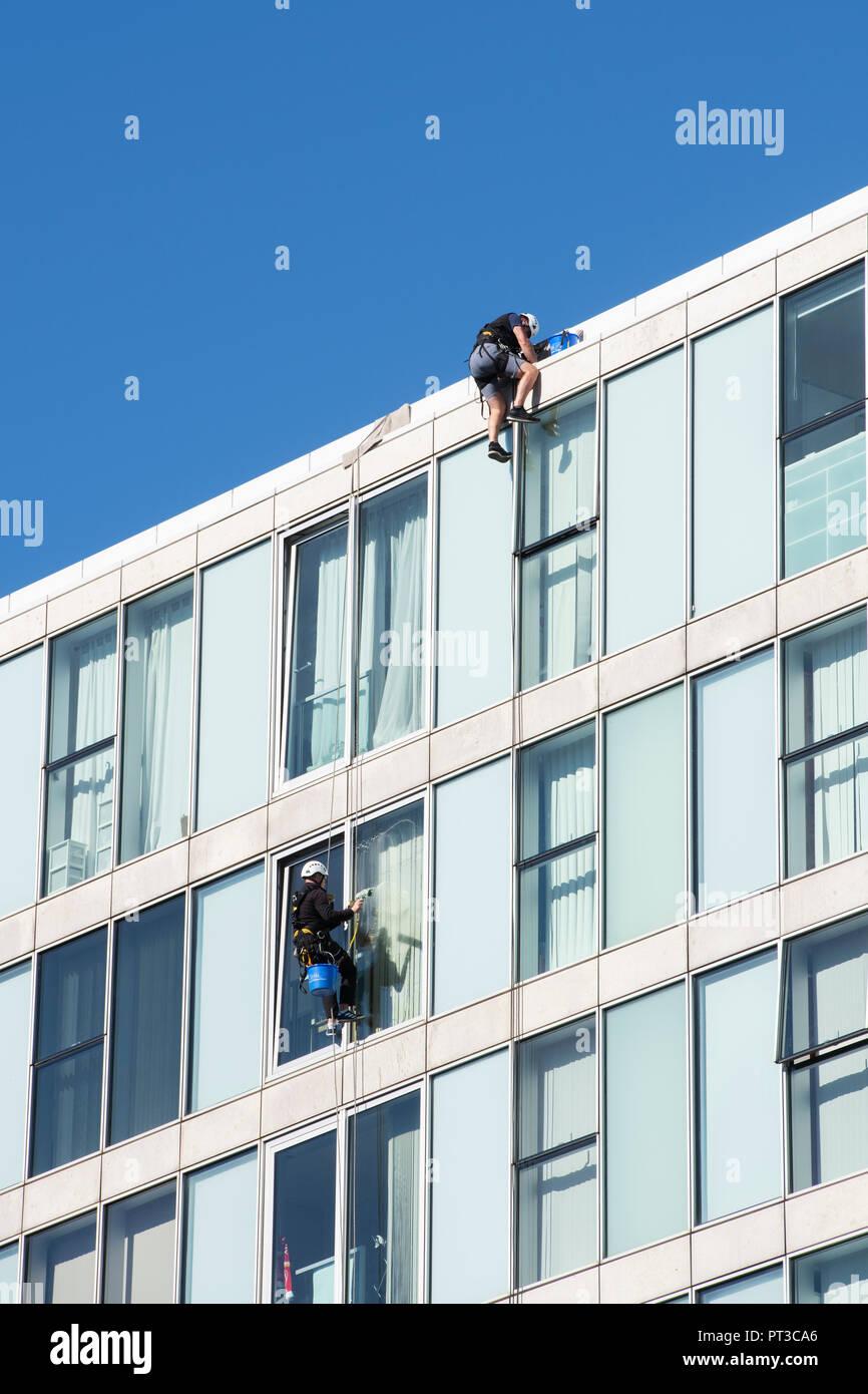 Window cleaners abseiling down an office building in Milton keynes, Buckinghamshire, UK Stock Photo