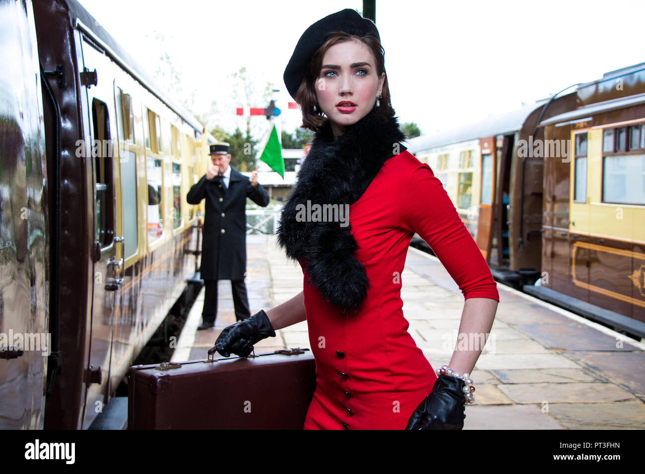 317376179700f Vintage beautiful female wearing red dress and black beret carrying  suitcases as she boards train at