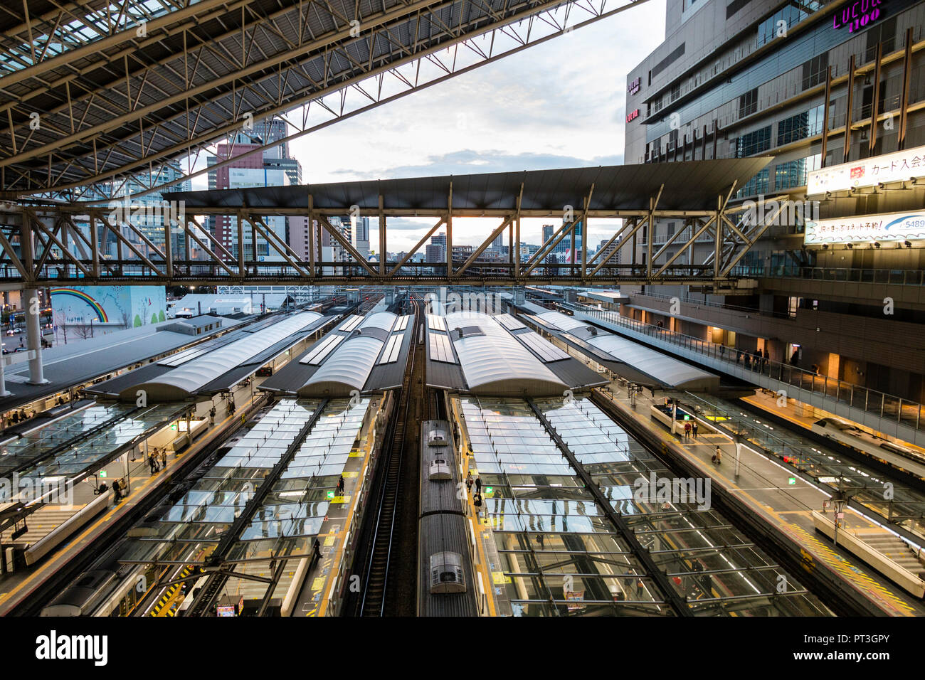 Osaka Station City. High angle view over the platforms and tracks with trains waiting at platforms. Early evening, platforms illuminated. - Stock Image