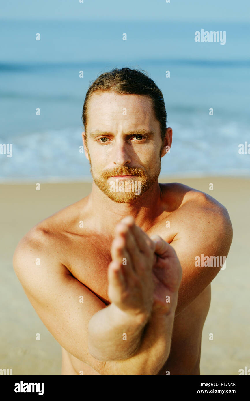 Long Hair Athletic Man With No Shirt Doing Yoga On Blue Mat At The