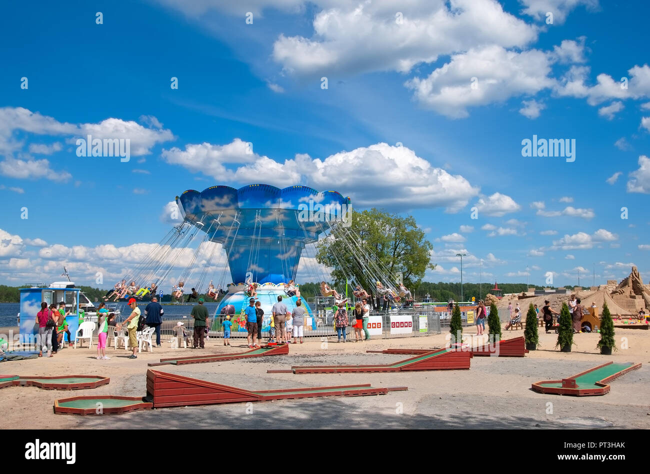 LAPPEENRANTA, FINLAND - JUNE 15, 2016: Adults look at the kids ride the attraction near Saimaa Lake. On the right side is Knight Sandcastle Stock Photo