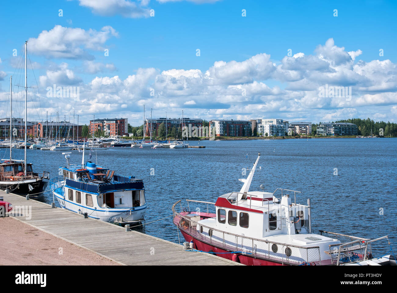 LAPPEENRANTA, FINLAND - AUGUST 8, 2016:  Pier with yachts and boats on Saimaa Lake. On the background are residential buildings on Rapasaari Island Stock Photo