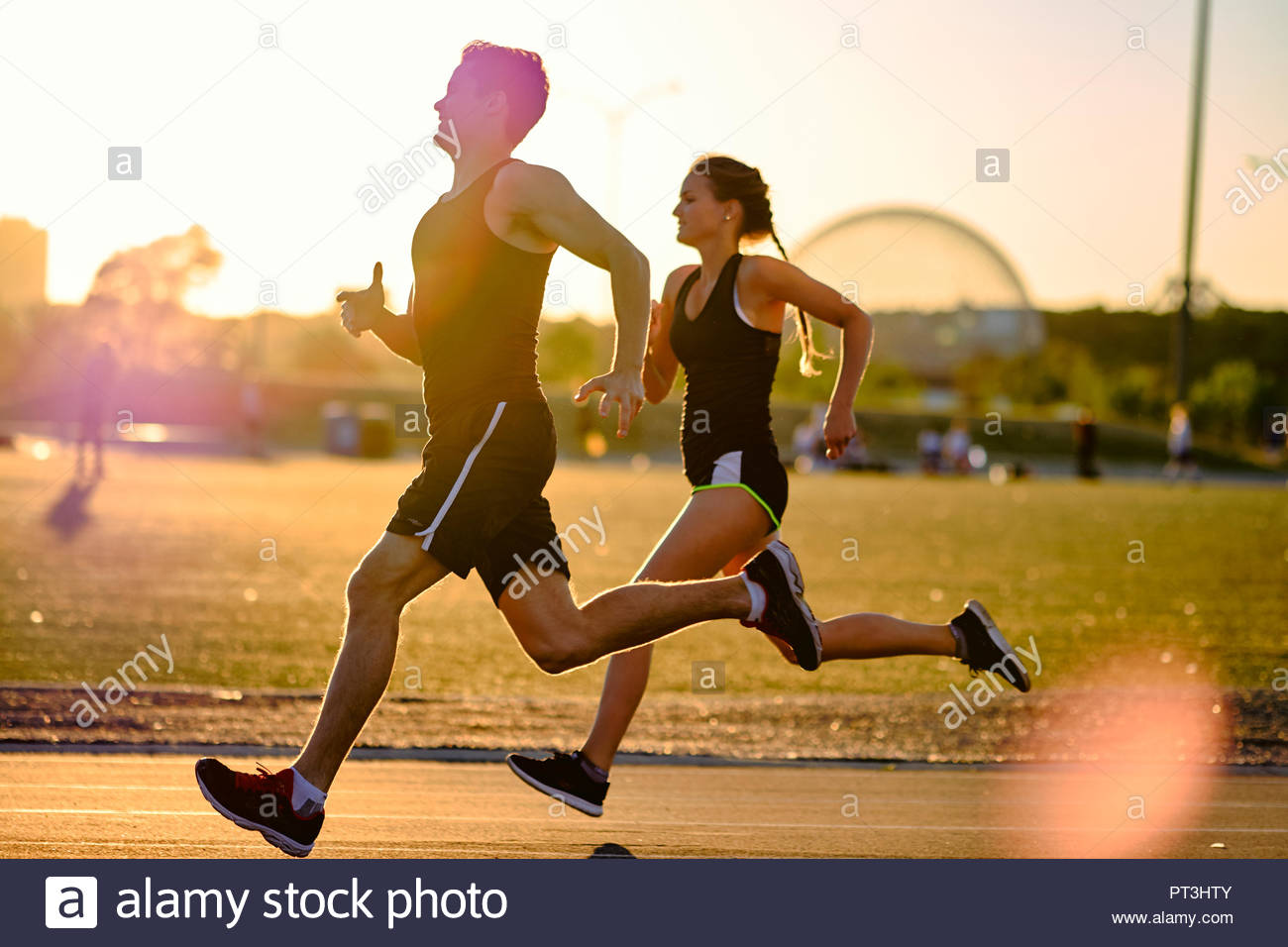 Sprinters racing around track during workout with sunset behind, Montreal, Quebec, Canada - Stock Image