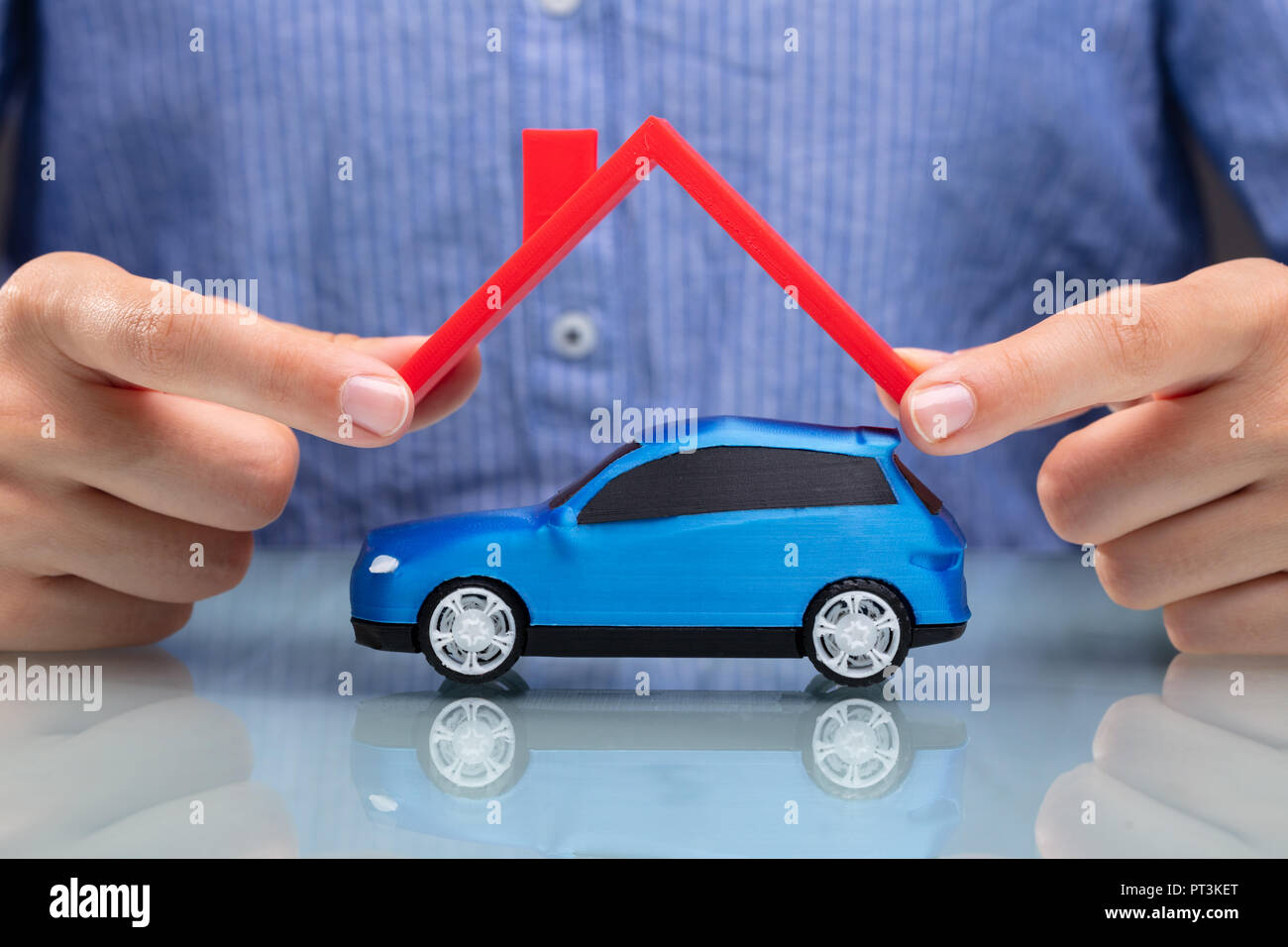Close-up Of A Businesswoman's Hand Protecting Blue Car With Red Roof - Stock Image