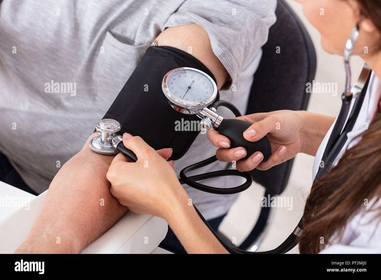 Close-up Of A Female Doctor's Hand Measuring Blood Pressure Of Patient - Stock Image