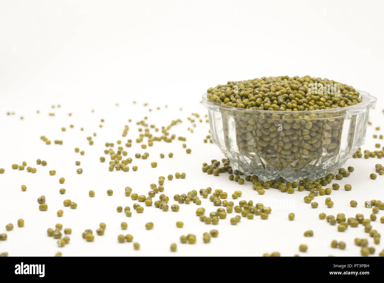 Green mung dal in transparent  bowl isolated on white background. - Stock Image