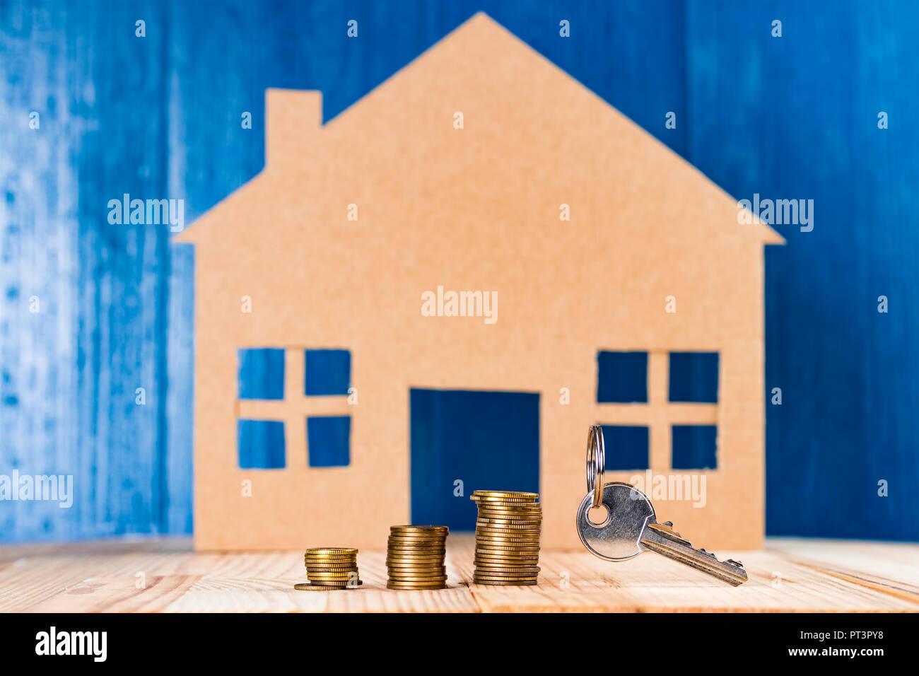 Stacks of coins money and door key against house shape and blue background. Household expenses or loan abstract concept. - Stock Image