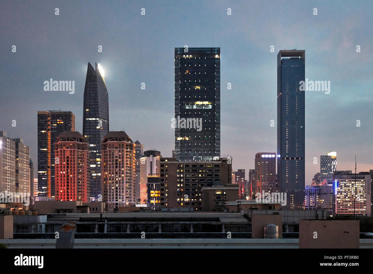 High-rise buildings in Futian District illuminated at dusk. Shenzhen, Guangdong Province, China. Stock Photo