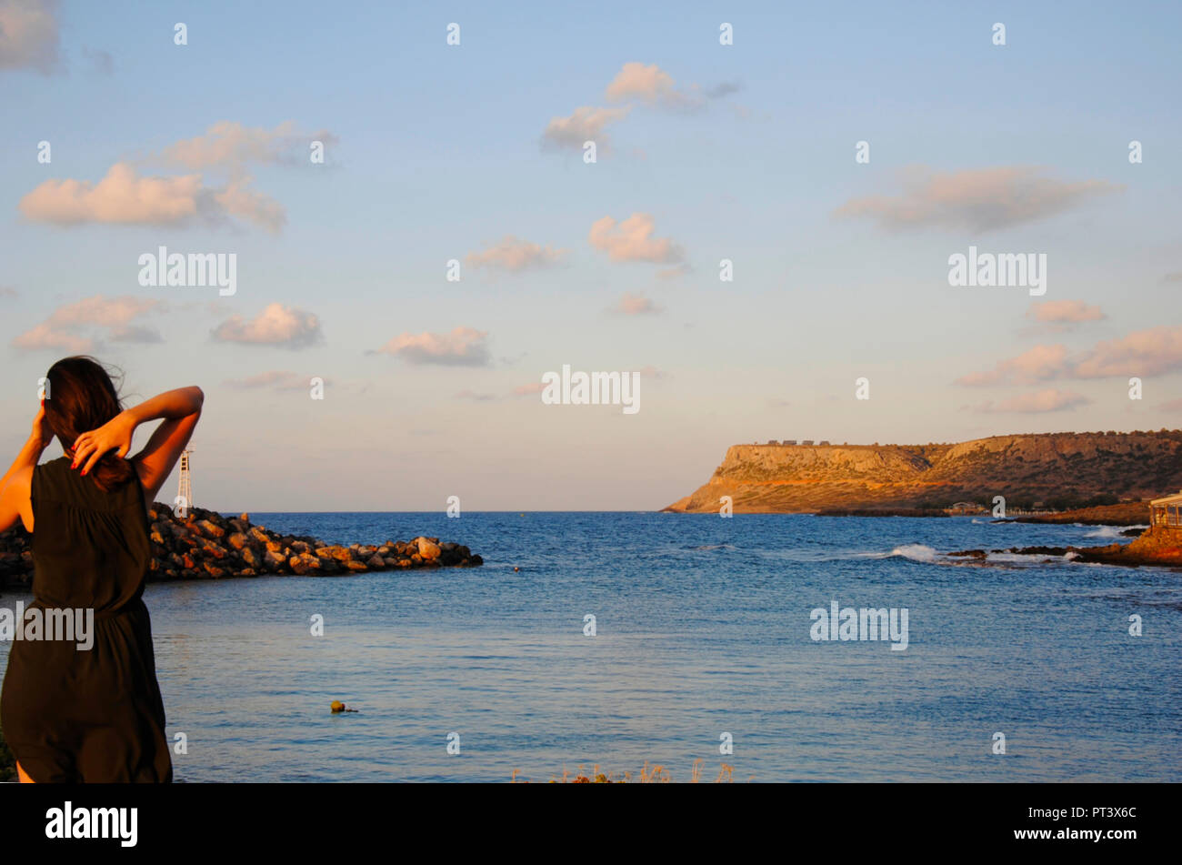 sunset with a girl looking onto the greek mediterranean sea - Stock Image