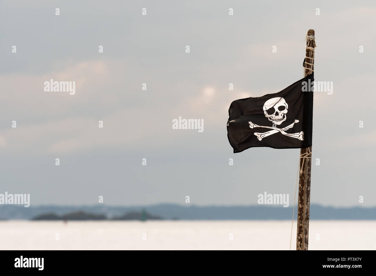 Small jolly roger on a wooden pole in front of cloudy sky - Stock Image