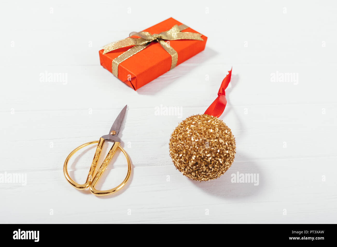 Close-up gold Christmas ball, scissors and red gift box on white wooden table, inclined top view. Stylish flat lay composition group of items to prepa - Stock Image