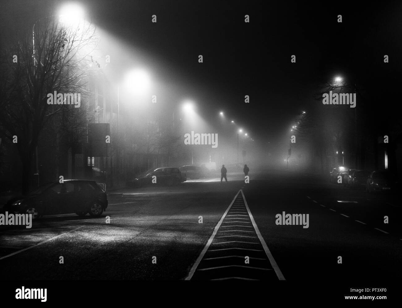 Cork City, Cork, Ireland.  11th December, 2016  Two people cross the street as early morning fog envelops the South Mall in Cork City, Ireland. - Stock Image