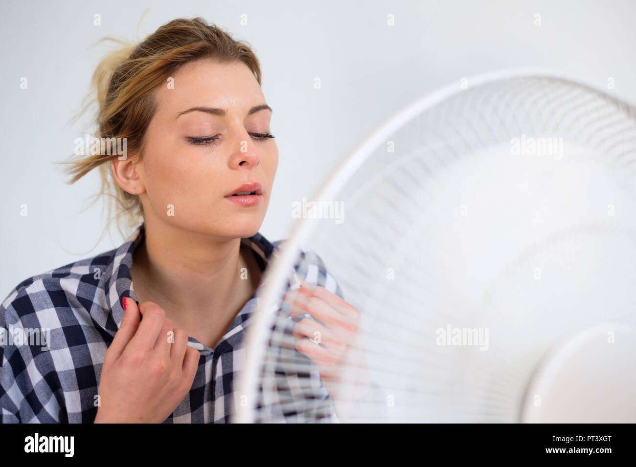 Girl trying to refresh from the summer heat haze - Stock Image