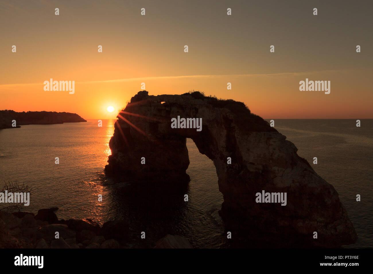 Europa Spanien Balearen Mallorca Südküste Santanyi - der Felsen Es Pontas bei Sonnenaufgang mit Lichtreflektion im Wasser und Sonne - Stock Image