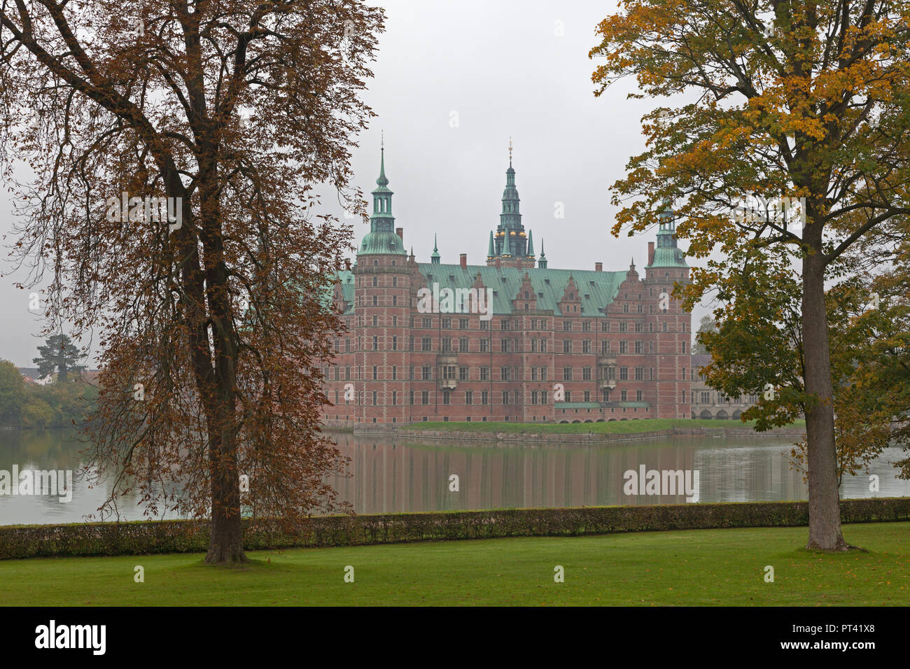 Frederiksborg Castle in Hillerød, North Sealand, Denmark, on a foggy autumn day Stock Photo