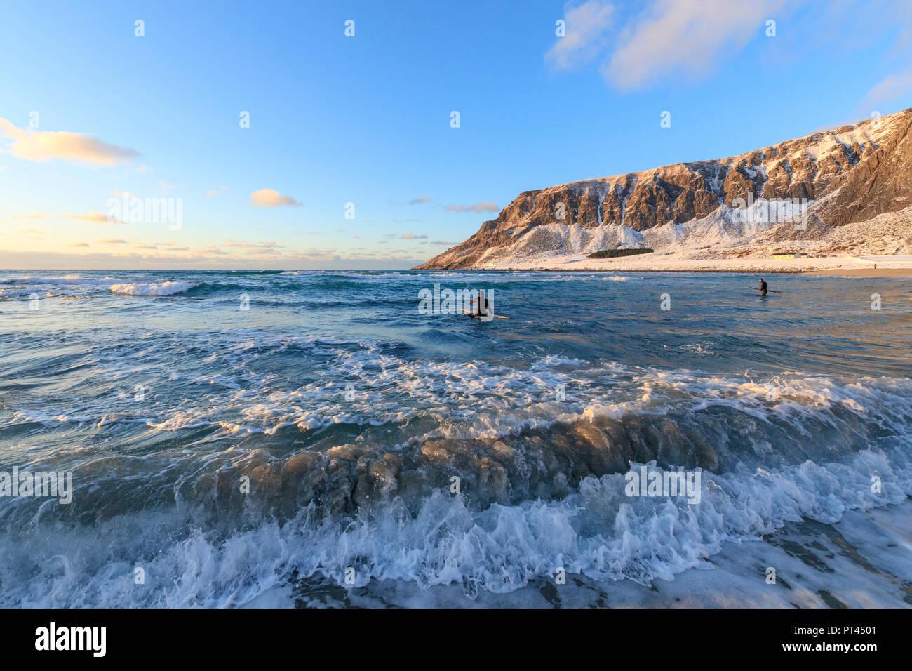 Surfers paddling, Unstad, Vestvagoy, Lofoten Islands, Norway - Stock Image