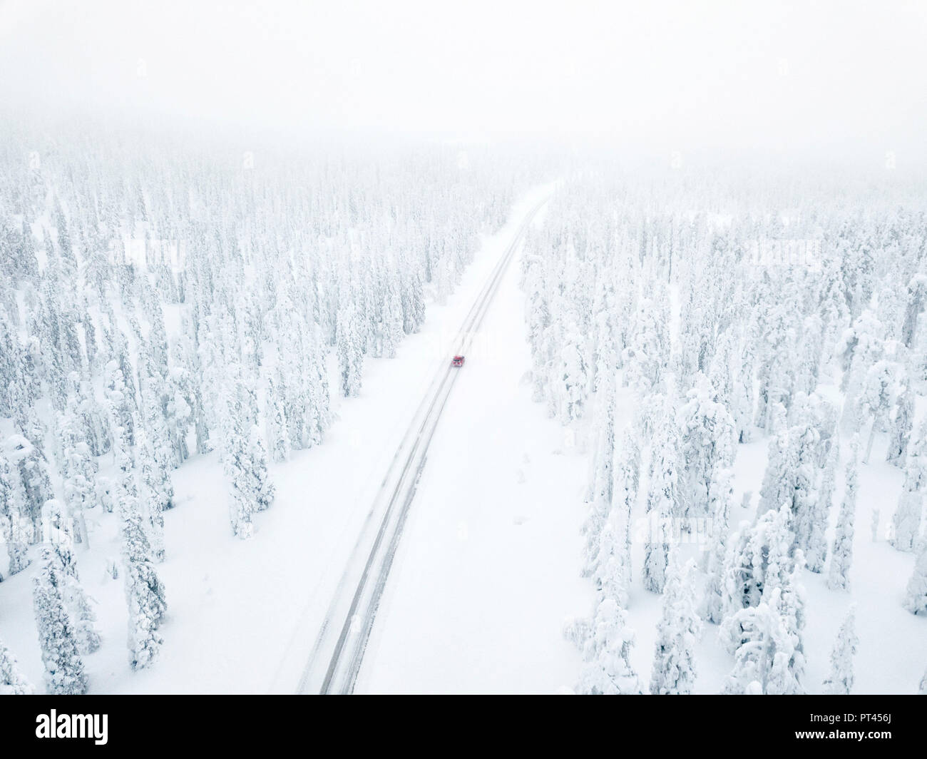 Aerial view of car along the snowy road in the icy forest, Pallas-Yllastunturi National Park, Muonio, Lapland, Finland - Stock Image