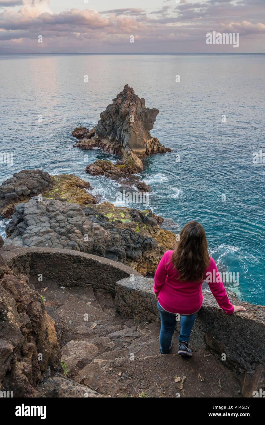 Woman observing the Atlantic Ocean and rock formations at dusk, Santa Cruz, Madeira region, Portugal, - Stock Image