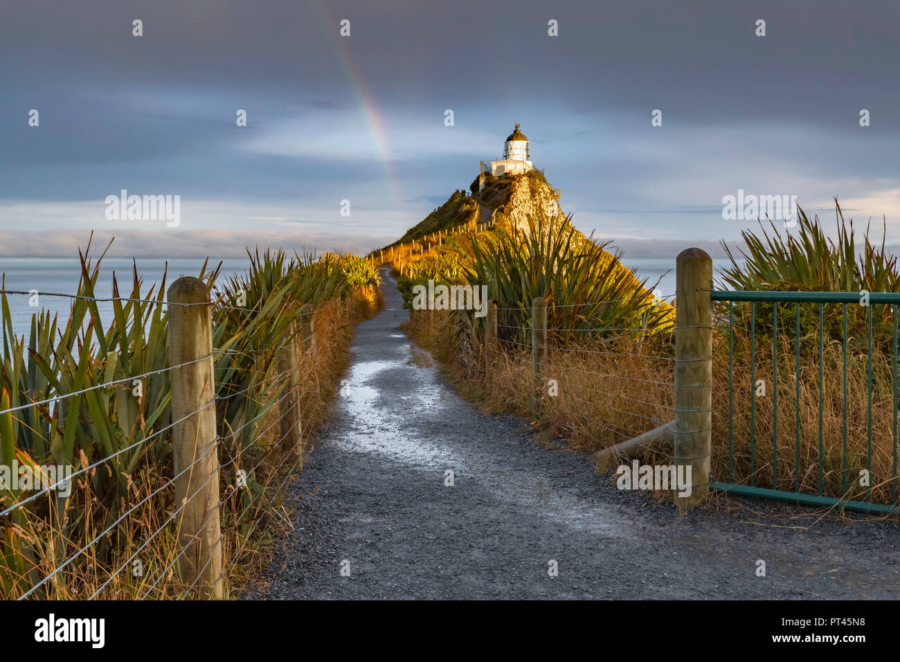 Rainbow at Nugget Point lighthouse after the storm, Ahuriri Flat, Clutha district, Otago region, South Island, New Zealand, - Stock Image