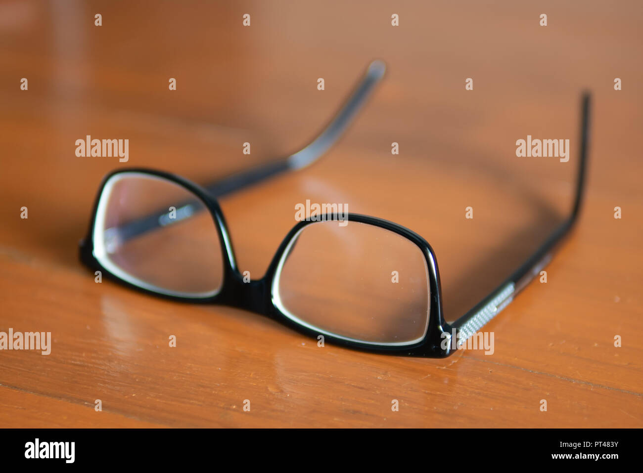 Eyeglasses on wooden table - Stock Image