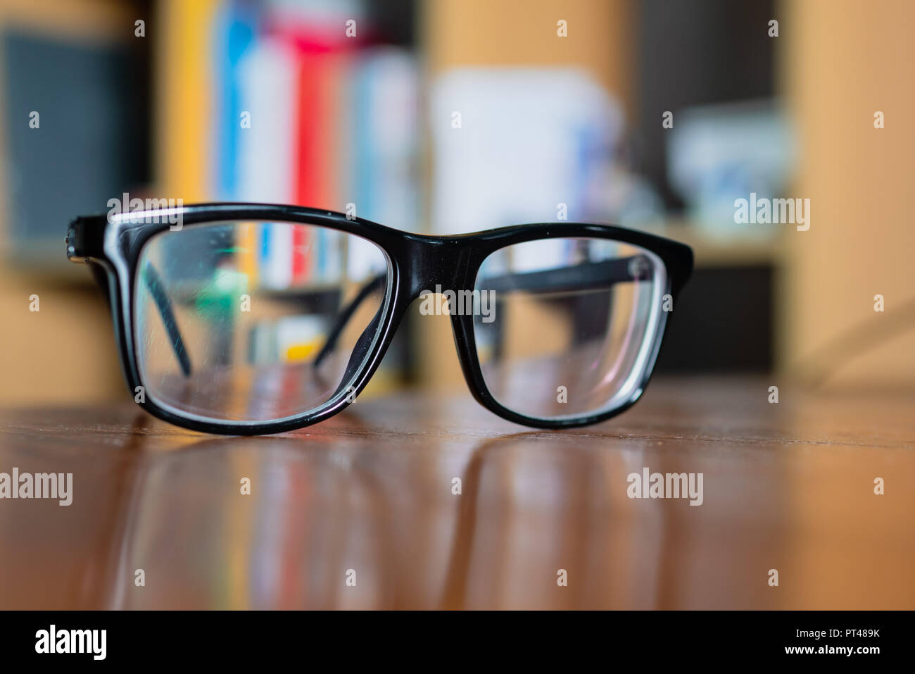 Eyeglasses on a table with bookshelf on background - Stock Image