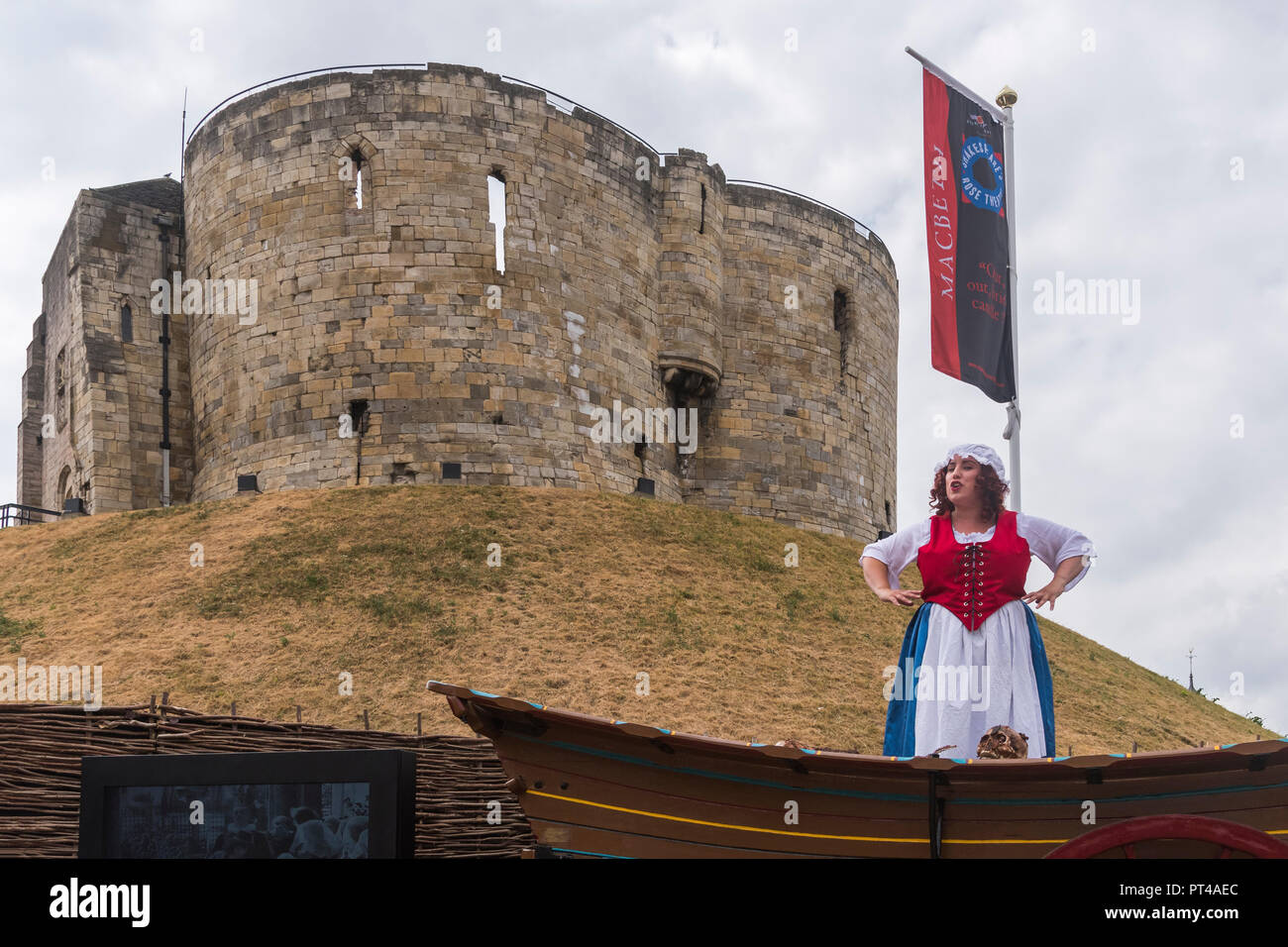 Female actress in costume (playing Mad Alice) giving live talk & performance on wagon in front of Cliffords Tower - York, Yorkshire, England, UK. - Stock Image