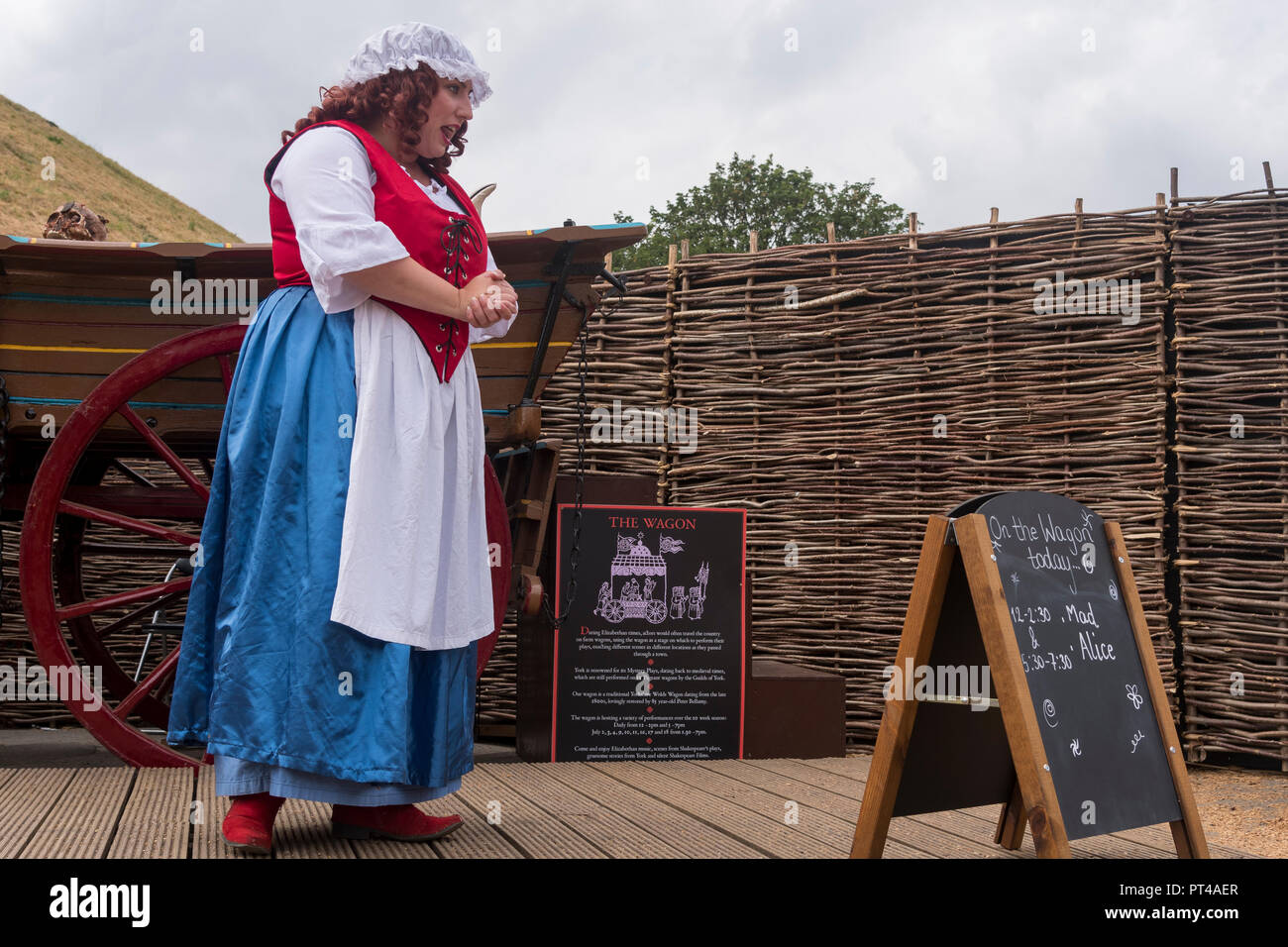 Female actress in historic costume & curly wig (playing Mad Alice) giving live talk & performance on stage, by wagon - York, Yorkshire, England, UK. - Stock Image